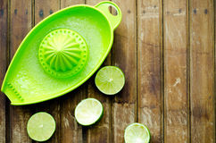 Green limes with green manual juicer on the table Royalty Free Stock Images