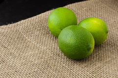 Green limes on a jute table cloth. Four green limes on a jute table cloth close up stock images