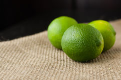 Green limes on a jute table cloth. Four green limes on a jute table cloth close up royalty free stock photography