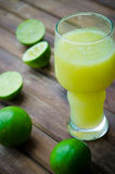 Green limes with lime juice in the glass Royalty Free Stock Photo
