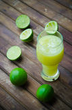 Green limes with lime juice in the glass Stock Photo