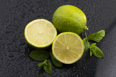 Green limes with mint and water drops Stock Images