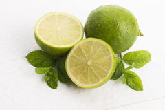 Green limes with mint and water drops Stock Photos