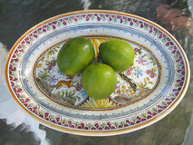 Green limes on plate. Three ripe green citrus limes on decorative plate Stock Photos