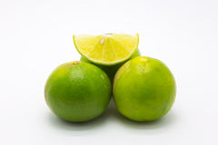 Green limes and slice on white Royalty Free Stock Photo