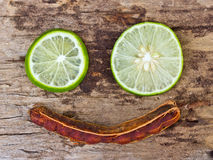 Green limes and tamarind on wooden background. Royalty Free Stock Images