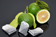Green limes with tea bags. Green lime with tea bags isolated royalty free stock photos