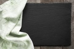 Green linen napkin on black slate dish. Top view. Stock Images