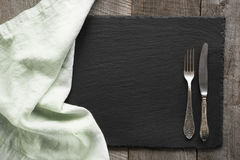 Green linen napkin and cutlery on black slate dish. Top view. Stock Image