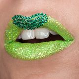 Green lips with sparkles covered with gemstones. Beautiful green lipstick on her lips, white teeth open mouth. Lip art stock images