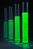 Green liquid in cylinders. Graduated cylinders with a green fluorescing liquid of different height on a dark grey background. Shallow depth of field Royalty Free Stock Photography
