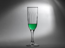 Green liquid in a glass cup on greyish background. Transparent green liquid in a glass cup on abstract grey background Royalty Free Stock Photos
