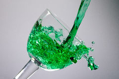 Green liquid puring in to a glass. On white background. Clean and artistic photo Royalty Free Stock Photo