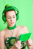 Green listener. Pretty brunette wearing headphones and checking her cd-box Stock Photos