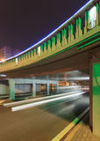 Green lit underpass with traffic in motion blur, Beijing night-time, China Stock Photo