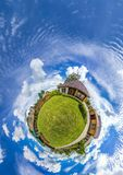 Green little planet panorama with architecture, soft blue sky and white clouds. Buildings at summer. Planet Earth. stock photography