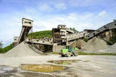 Green loader in the production of rubble. Mound of rubble at the Stock Photos