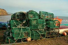 Green Lobster cages drying on shore. Green lobster cages drying on the shores in Robin Hood`s Bay, Yorkshire, England.  Several dozen piled on top of each other Royalty Free Stock Photo