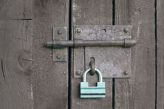 Green lock on a grey wooden door Royalty Free Stock Images
