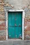 Green locked door. An old well used green painted door with a locked padlock in a crumbling old characterful brick wall stock photos