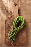 Green long bean-2. Green long bean, tied with brown rope, on a wooden plate and brown canvas Royalty Free Stock Photos
