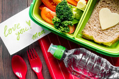 Green lunch box for kid on wooden background top view Stock Photography