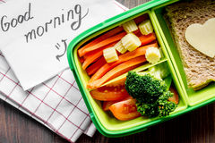 Green lunch box for kid on wooden background top view Stock Images
