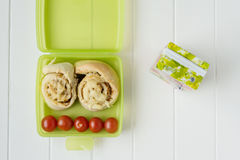 Green lunchbox with scrolls and tomato Stock Photos