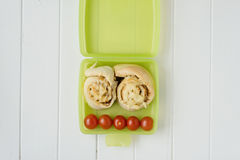 Green lunchbox with scrolls and tomato Royalty Free Stock Photography