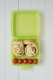 Green lunchbox with scrolls and tomato Royalty Free Stock Photo