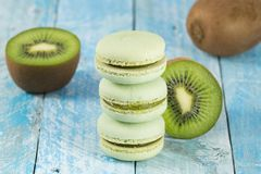 Green macarons and fresh kiwis. Three green macarons and fresh kiwis on blue wooden background royalty free stock images