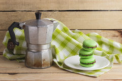 Green macarons on the plate, coffee pot and plaid napkin. Soft focus background Stock Images