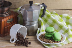 Green macarons on the plate, cup, coffee pot and plaid napkin. Green macarons on the plate, cup, coffee pot, plaid napkin and coffee beans, soft focus background Stock Image
