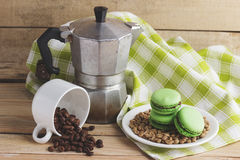 Green macarons on the plate, cup, coffee pot and plaid napkin. Green macarons on the plate, cup, coffee pot, plaid napkin and coffee beans, soft focus background Stock Photos