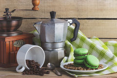 Green macarons on the plate, cup, coffee pot and plaid napkin. Green macarons on the plate, cup, coffee pot, plaid napkin and coffee beans, soft focus background Royalty Free Stock Images