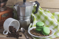 Green macarons on the plate, cup, coffee pot and plaid napkin. Green macarons on the plate, cup, coffee pot, plaid napkin and coffee beans, soft focus background Royalty Free Stock Image
