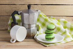 Green macarons on the plate, cup, coffee pot and plaid napkin. Soft focus background Royalty Free Stock Photos
