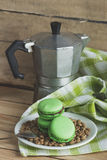 Green macarons on the plate with green coffee beans, coffee pot and plaid napkin. Soft focus background Stock Photos