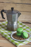 Green macarons on the plate with green coffee beans, coffee pot and plaid napkin. Soft focus background Royalty Free Stock Photo