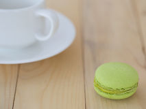 Green Macaroon , Macaron with cup on wooden background. Green Macaron , Macaroon with cup on wooden background royalty free stock images