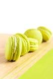 Green macaroons arranged diagonally on wooden table Stock Photo
