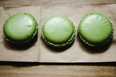Green macaroons with delicious taste on craft paper on wooden ba. Ckground Stock Photography
