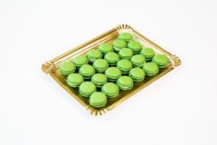 Green macaroons on a gold tray with white background stock photos