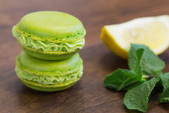 Green macaroons with lemon and mint in background Royalty Free Stock Photography