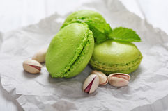 Green macaroons. With pistachio over wooden background Royalty Free Stock Photography
