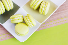 Green macaroons on a square plate. Top view. Top view of some green macaroons with cream ganache on square plate Royalty Free Stock Photos