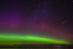 Green, magenta and purple aurora borealis with meteor over a lake in North Dakota. Green, magenta and purple aurora borealis with a shooting star over Long Lake Royalty Free Stock Images