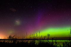 Green, magenta and purple aurora borealis with meteor Royalty Free Stock Images