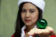 Green magic ball on the hand of out focus Asian Santa Girl Dress. royalty free stock image