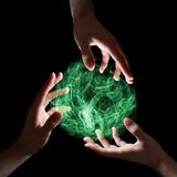 Green magical sphere. Emerald magical sphere held by three hands Stock Photo